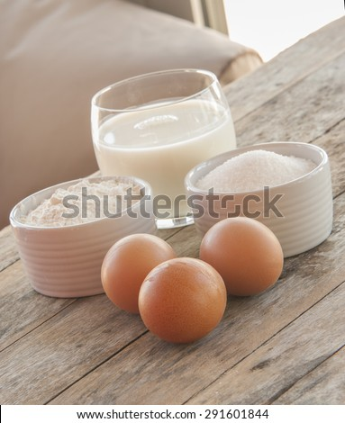 Ingredients for pancakes - eggs, flour, milk on wooden background.