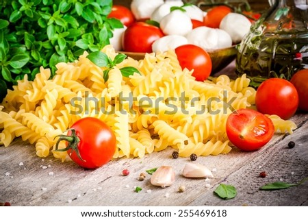 Ingredients for pasta: organic cherry tomatoes, mozzarella, fresh basil, fusilli, garlic and olive oil on a rustic wooden background - stock photo