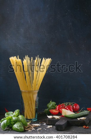 Ingredients for pasta sauce tomatoes, basil, garlic, chili peppers and parmesan cheese with dry spaghetti on wooden cutting board over black textured background.  - stock photo