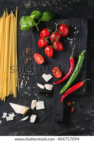 Ingredients for pasta sauce tomatoes, basil, garlic, chili peppers and parmesan cheese with dry spaghetti on wooden cutting board over black textured background. Top view - stock photo