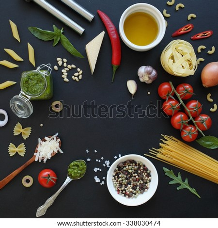 Ingredients for pasta sauces and raw pasta on black board. Food frame with free space in the middle. - stock photo