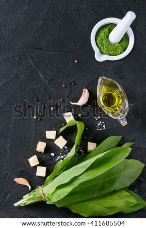 Ingredients for pesto and ramson pesto in ceramic mortar. Bunch of ramson, olive oil, parmesan cheese, garlic, salt and pepper over black textured background with copy space. Flat lay - stock photo