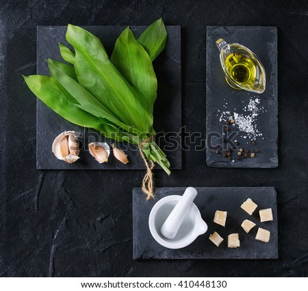 Ingredients for pesto. Bunch of ramson, olive oil, parmesan cheese, garlic, salt and pepper on slate boards over black textured background. Flat lay - stock photo