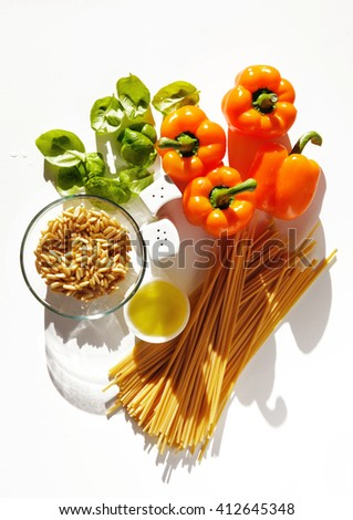 ingredients for pesto pasta spaghetti sweet orange, spaghetti pasta, bell peppers, pine nuts, basil leaves, olive oil - stock photo
