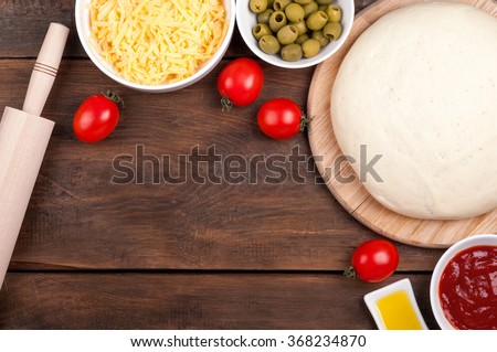 Ingredients for pizza. Dough, rolling pin, cherry tomatoes, olive oil, olives, tomato sauce and cheese on a wooden table. Cooking pizza. View from above - stock photo
