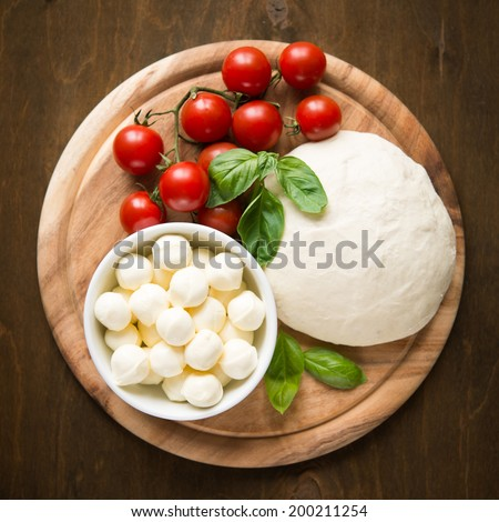 Ingredients for pizza margherita on wooden plate top view - stock photo