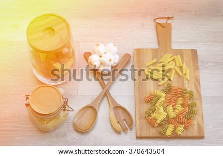 Ingredients for preparing macaroni  on a table with wood spoon and fork .jpg - stock photo