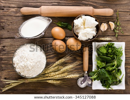 Ingredients for ravioli with spinach and ricotta cheese on wooden background - stock photo
