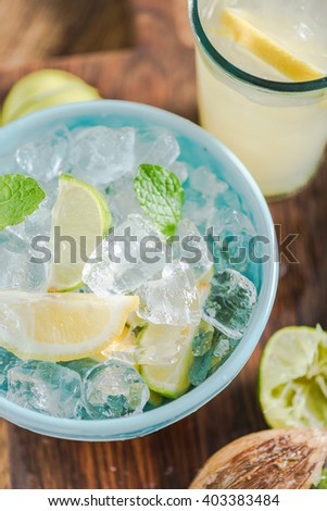 Ingredients for refreshing lemonade for hot summer days, lime and lemons, ice and mint in vintage jar.