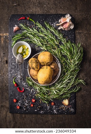 Ingredients for rosemary Potatoes with spices, garlic and oil on dark wooden and slate background, top view - stock photo
