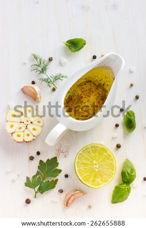 Ingredients for salad dressing. Olive oil, garlic, lemon, herbs and spices on white background, top view - stock photo