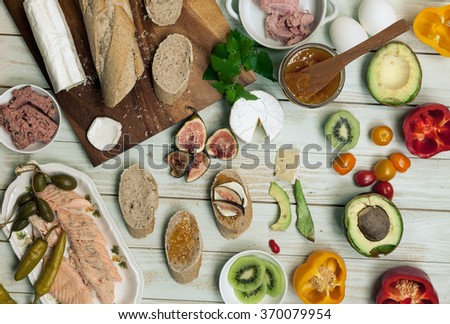 Ingredients for sandwich, build your own tartines, Small and simple cocktail snacks with various toppings, goat cheese, slices smoked salmon, boiled eggs, smoked meat, baguette. Top view, rustic style - stock photo