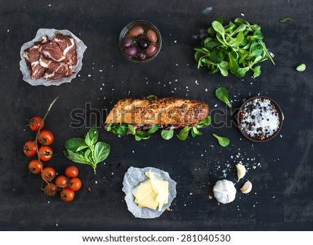 Ingredients for sandwich with smoked meat, baguette, basil, arugula, olives, cherry-tomatoes, parmesan cheese, garlic and spices over black grunge background. Top view - stock photo