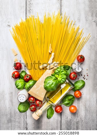 Ingredients for spaghetti with tomato sauce on white wooden table, top view - stock photo