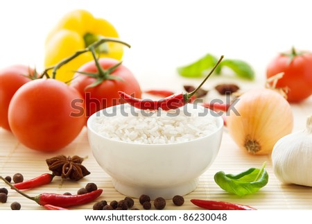 Ingredients for spicy Asian food with a bowl of uncooked basmati rice, fresh vegetables and spices. - stock photo