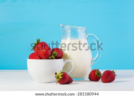 ingredients for strawberry milkshake: rustic fresh milk in a glass jar and raw ripe fresh strawberries in a white cup on a white wooden table on a blue background - stock photo