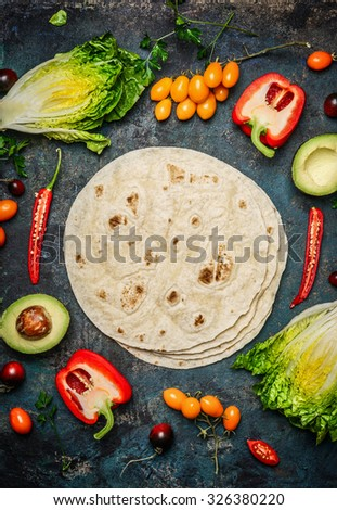 Ingredients for tacos or burrito making.  Fresh organic vegetables and tortillas on rustic background, top view, place for text - stock photo
