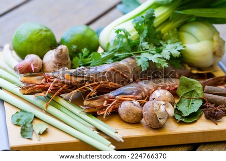 Ingredients for Thai tom yam soup laid out on a kitchen counter with tiger prawns, mushrooms, ginger, lemongrass, limes, celery, parsley and spices - stock photo