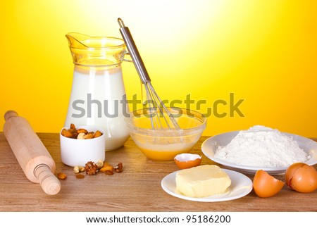 Ingredients for the dough wooden table on yellow background