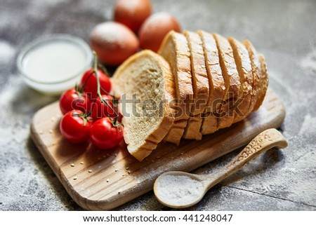 Ingredients for the preparation of bakery products. Bread, flour, eggs and cherry tomatoes.