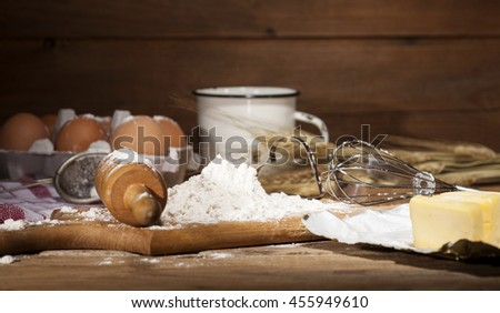 Ingredients for the preparation of bakery products - milk, eggs, butter, flour - on rustic wooden background.