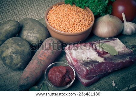 Ingredients for Turkey vegetable soup with red lentils, lying on an old wooden board and sacking. Tinted - stock photo