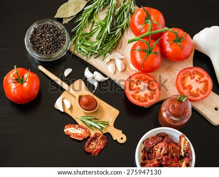 Ingredients. Fresh tomatoes, Sun-dried tomatoes, Tomato Sauce and Spices on dark background. Cooking concept. Healthy foods. - stock photo