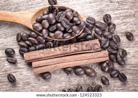 Ingredients of coffee beans and cinnamon in wooden spoon