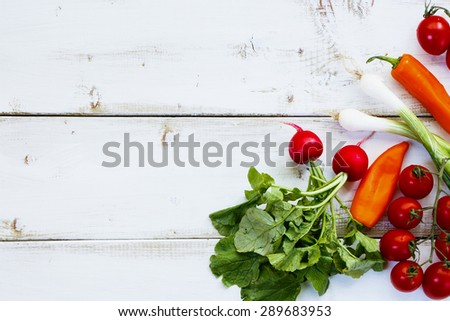 Ingredients of Fresh vegetable salad on white wooden background. Healthy or vegetarian eating concept.