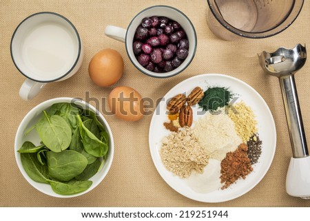 ingredients of healthy breakfast smoothie: almond milk, raw eggs, fresh spinach, frozen blueberries, whey protein, cacao, chia, pecans, maca root, spirulina, collagen protein, spices with a  blender - stock photo