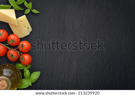 Ingredients of italian cuisine  - cherry tomato, basil, parmesan and olive oil - on dark background - stock photo