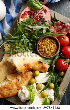 Ingredients of Mediterranean cuisine, on wooden tray, on wooden background - stock photo