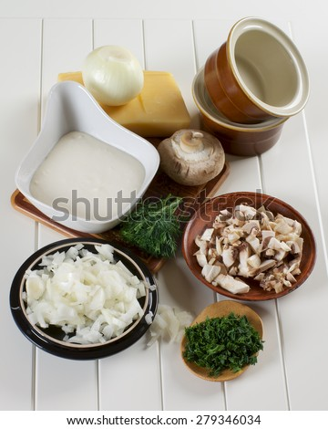 Ingredients of Mushroom Julienne with Raw Chopped Champignon Mushrooms, Onion and Dill with Bechamel and Cheese closeup on Plank White background - stock photo
