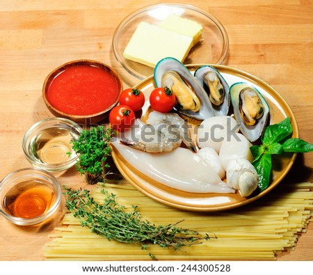 ingredients of seafood pasta: squid, mussel, shrimp, shellfish,scallops , tomato, spaghetti, garlic, oil, butter, rosemary, basil, thyme - stock photo