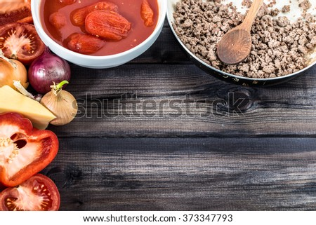 Ingredients of spaghetti bolognese arranged on wooden table.