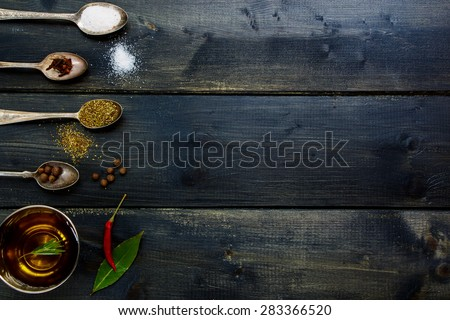 Ingredients - olive oil, herbs and spices, old metal spoons and dark wooden background - cooking, healthy eating. Top view. - stock photo
