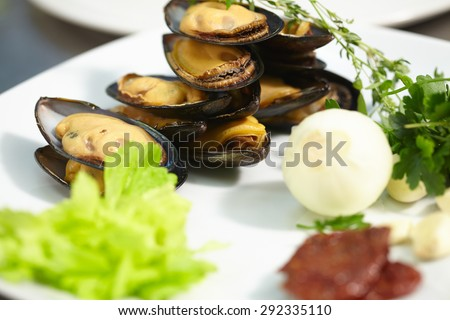 ingredients on the plate: mussels, onions, garlic, herbs