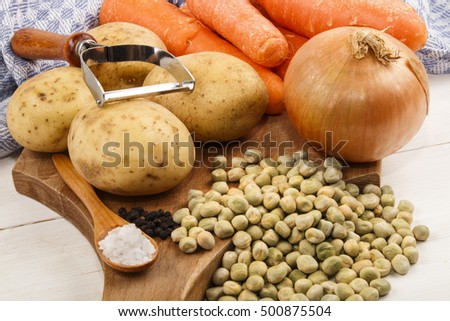 ingredients such as carrots, potatoes, onions, black peppercorns, coarse salt and dried peas to cook a vegetarian pea soup