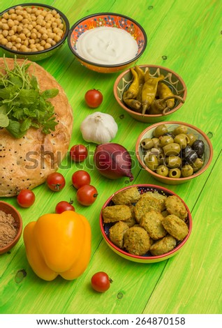 Ingredients to make a turkish sandwich with falafel, lettuce, pepper and mint yogurt sauce - stock photo