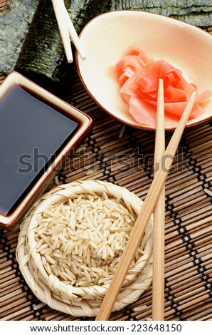 Ingredients to Preparing Sushi  with Nori, Ginger, Rice, Soy Sauce and Chopsticks on Bamboo Straw Mat. Top View - stock photo