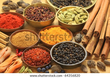 Ingredients - warm colours of herbs and spices. Cinnamon sticks, cardamon, allspice, clove, mace, fenugreek, coriander and juniper