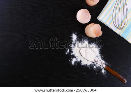 Ingredients with wooden spoon and scattered flour - stock photo