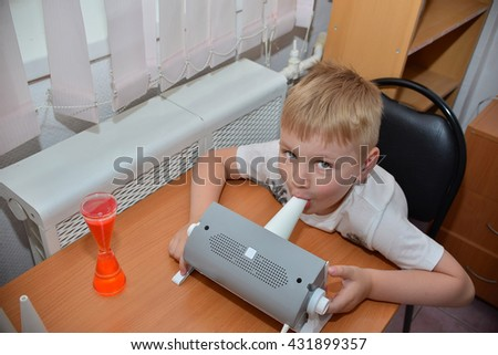inhalation by a. a child in a mask by a nebulizer for inhalation during asthmatic attack. medical therapy if difficulty breathing, asthma, respiratory diseases