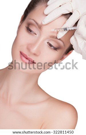 INJECTION AND WOMAN BEAUTY FACE.Beauty injections. Portrait of a woman close-up,perfect skin on her face,her doing a shot in the forehead between the eyebrows. woman on the procedures of youth