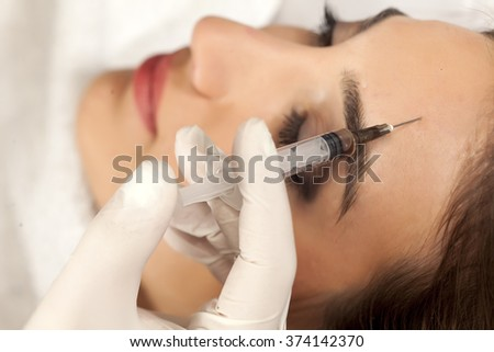 Injection in forehead - stock photo