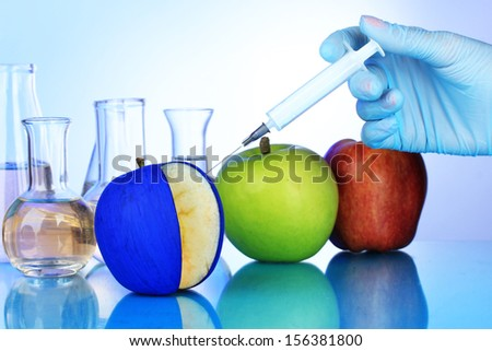 Injection into apple on blue background