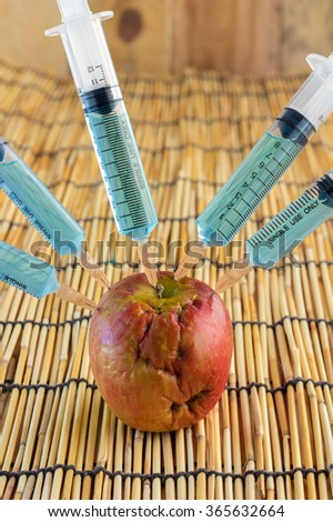 Injection into red apple - Concept for Genetically modified fruit and syringe with colorful chemical GMO food on bamboo mat background - stock photo