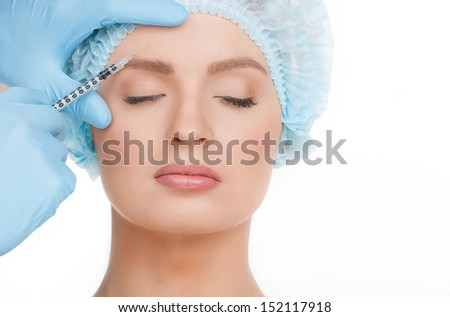Injection. Portrait of beautiful young woman in medical headwear keeping eyes closed while doctors hands in gloves making a botox injection in her face isolated on white