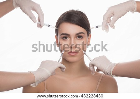 Injections of botox, woman having beauty treatment. Doctors injecting in beautiful face of young woman. Plastic surgery concept.