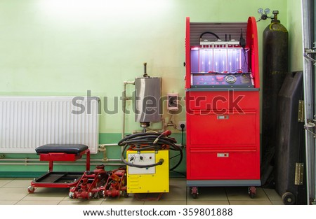 Injector repairing machine in workshop car service station - stock photo